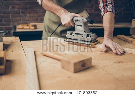 closeup photo of cabinetmaker grinds wooden plank on tabletop at workstation poster