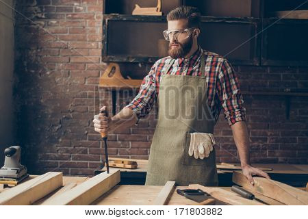 Concenrated Handsome Cabinetmaker With Chisel Think. Stylish Craftsman With Brutal Hairstyle And Gla