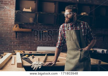 Bearded Handsome Joiner  Think And Look To The Side Near Tabletop With Tools.  Stylish Craftsman Wit