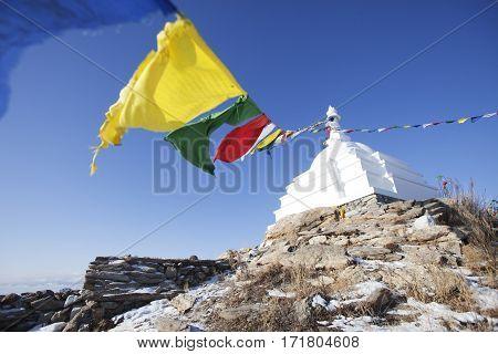 White Buddhist stupa with colorful flags. Olkhon island. Baikal landmark. Russia