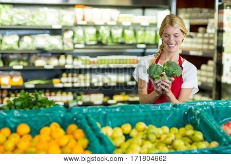 Female staff holding broccoli in organic section