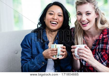 Portrait of cheerful young female friends with coffee cup at home