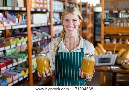 Smiling female staff holding jars of honey in supermarket