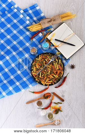 Open Notebook With Pen And Pasta On Blue Plaid Tablecloth