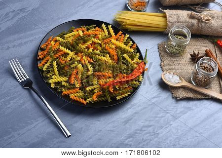 Fusilli Pasta In Bowl With Fork And Spaghetti Bunch