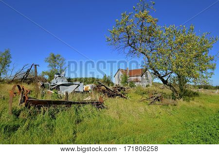 A former family farm, machinery, and house have fallen into a state of ruins and disrepair.