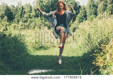 Young Woman happy jumping up summer vacations forest landscape on background Lifestyle Travel fun emotions success concept outdoor