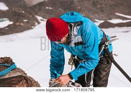 Man climber packing backpack mountains alpinism equipment Travel Lifestyle concept adventure active vacations outdoor mountaineering sport