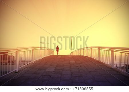 Woman running crossing a bridge next to the beack at sunset. Empty copy space for Editor's text.