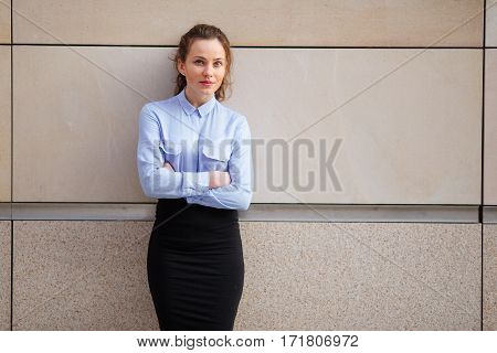 Brunette smiling woman standing near the wall of building, looking forward into camera