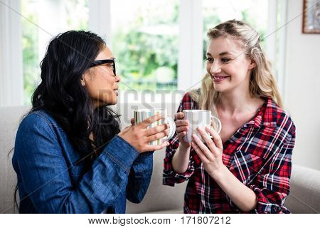 Close-up of female friends drinking coffee while sitting on sofa at home