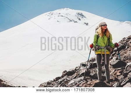 Woman traveler with backpack hiking in mountains Travel Lifestyle adventure concept active vacations outdoor mountaineering sport success Elbrus mountain on background