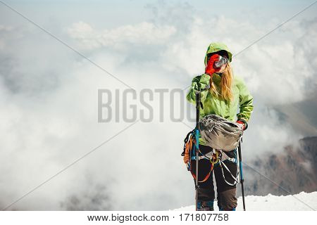 Woman alpinist drinking tea on mountain summit Travel Lifestyle adventure concept active vacations outdoor climbing sport