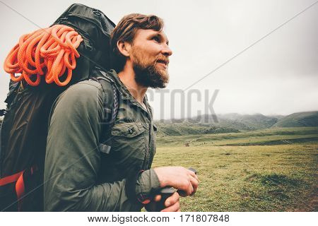 Traveler Man wayfaring in foggy mountains Travel Lifestyle concept adventure active vacations outdoor hiking sport with backpack climbing equipment