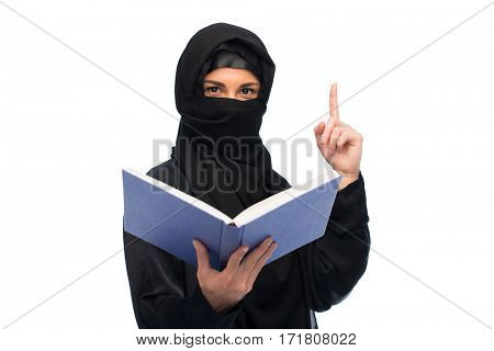 religion, education and people concept - muslim woman in hijab with book pointing finger up over white background