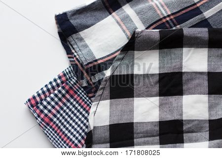 laundry, clothes, fashion and objects concept - close up of checkered shirt on white background