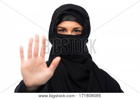 gesture, religious prohibition and people concept - muslim woman in hijab showing stop sign over white background