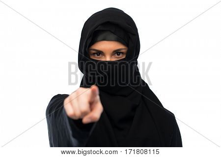religious and people concept - muslim woman in hijab pointing finger to you over white background