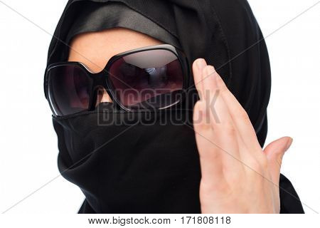 accessory, fashion and people concept - close up of muslim woman in hijab and sunglasses over white background