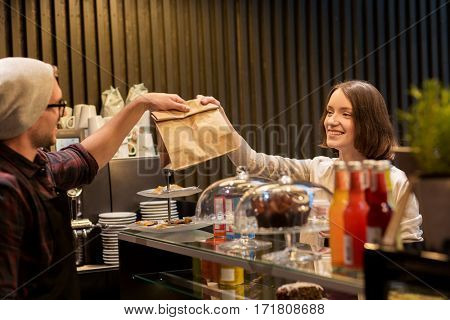 small business, food, people and service concept - happy man or barman giving paper bag to female customer at vegan cafe