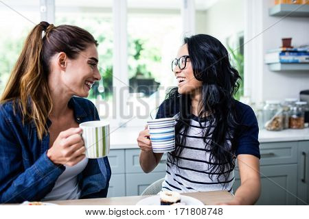 Close-up of young female friends laughing while drinking coffee at home