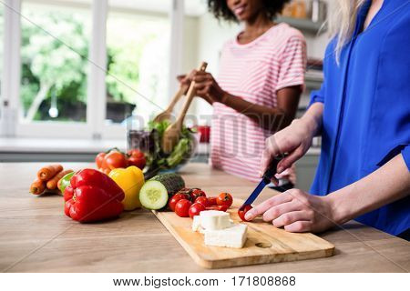 Midsection of female friends preparing food at table in kitchen
