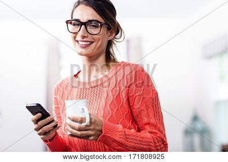 Portrait of happy young woman with mobile phone and mug at home