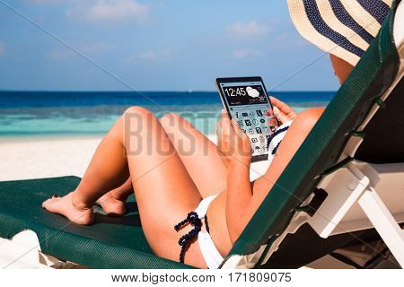 Woman on vacation lies in a sun lounger on the beach with a tablet in hands.
