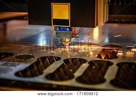 CNC Laser cutting of metal, modern industrial technology. . Small depth of field. Warning - authentic shooting in challenging conditions. A little bit grain and maybe blurred.