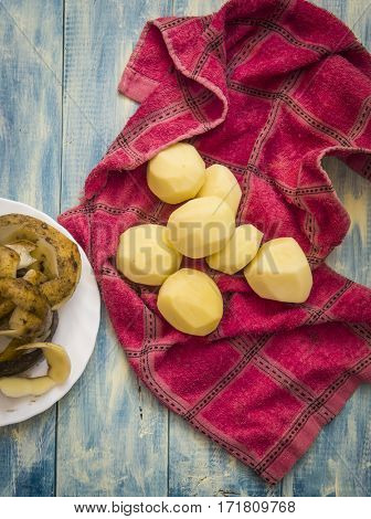 Potato food . The peeled potatoes and knife on wooden background .  Top view