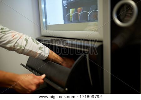 sell, technology, people and consumption concept - hand taking purchase from vending machine take-out port