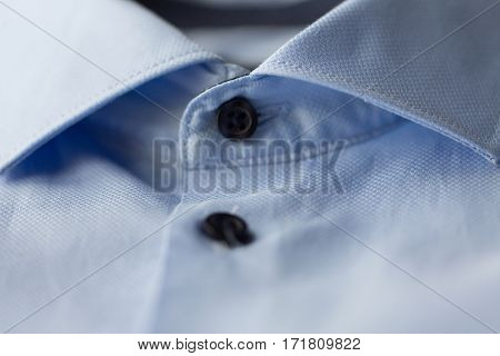 clothing, formal wear, fashion and objects concept - close up of blue shirt collar