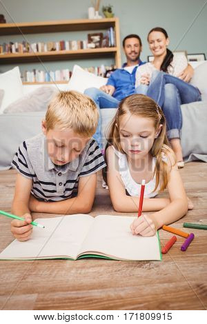 Children drawing on book while parents looking at them from sofa in living room