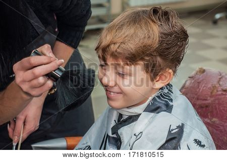Hairdresser brushing the boy's face thick brush after hair cutting