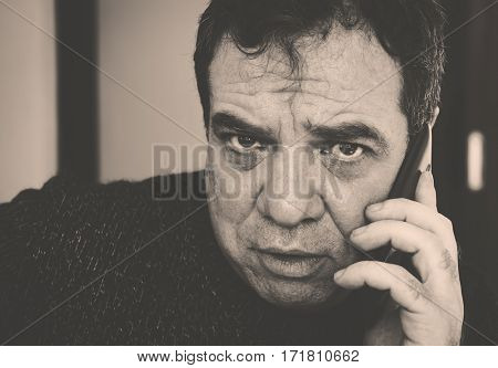 Vintage style black and white photo. Bad news. Sad man talking on a cell phone.