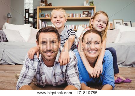 Portrait of happy parents lying on floor while children sitting on their back at home
