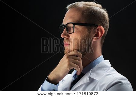 healthcare, people, profession and medicine concept - close up of male doctor in white coat over black background