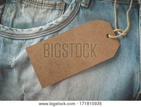 Closeup jeans with blank cardboard price tag for your text