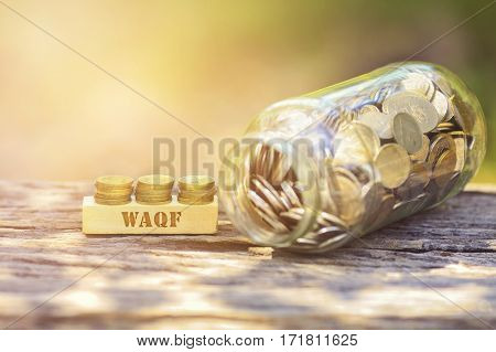 Waqf Word Golden Coin Stacked With Wooden Bar On Shallow Dof Green Background.