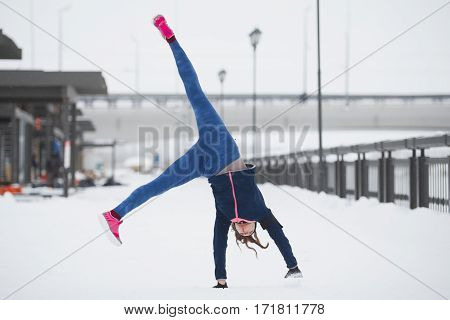 Fitness girl have acrobatic work out fitness at snow winter promenade, telephoto