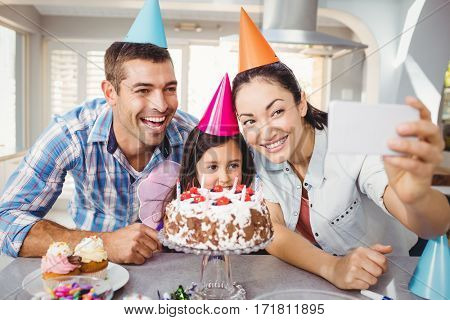 Close-up of happy family taking selfie during birthday celebration at home