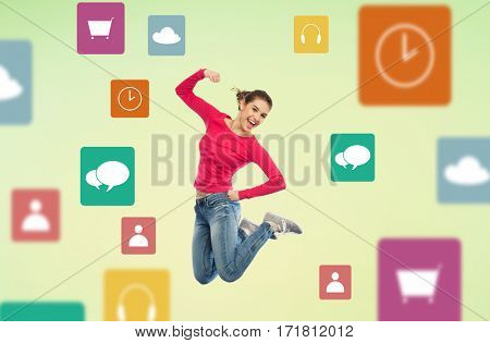 media and people concept - smiling young woman jumping in air with raised fist over green background and menu icons