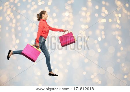 sale, motion and people concept - smiling young woman with shopping bags running in air over holidays lights background