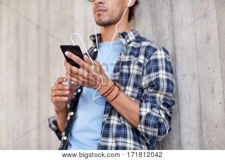 people, technology and lifestyle - close up of young hipster man with earphones and smartphone listening to music