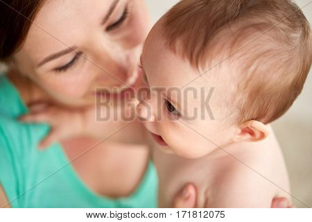 family, child and parenthood concept - close up of happy smiling young mother with little baby at home