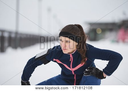 Woman runner stretching legs before run at snow winter promenade. Fitness concept., close up, telephoto