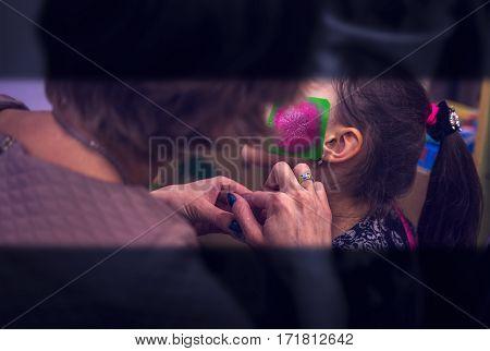 body art patterning on the girl's face. Aqua make-up.