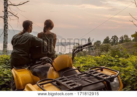 Beautiful Couple Is Watching The Sunset From The Mountain Sitting On A Quadbike.