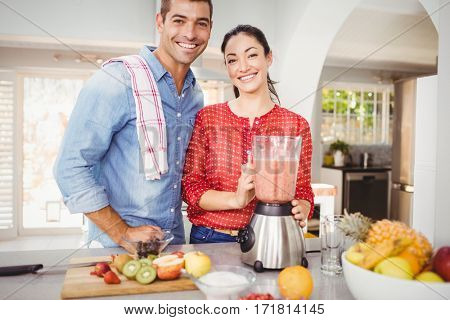 Portrait of happy couple with fruit juice while standing at home