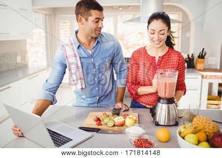 Couple standing with fruit juice while using laptop at home